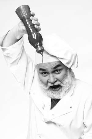 catsup bottle: Bearded chef with ketchup bottle and emotional face in white uniform and hat, black and white Stock Photo