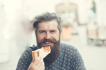 handsome sexy bearded young man hipster with long beard and mustache on smiling hairy face eating pizza on street outdoor