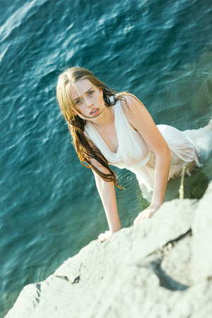 wet dress: young pretty woman in white wet dress in water near stone sunny day outdoor on natural background