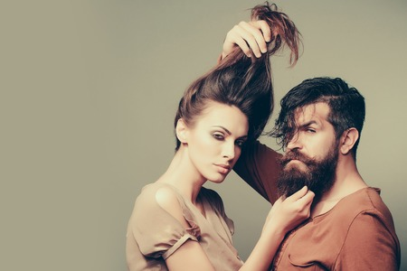young sexy couple of woman with pretty face and brunette hair in blouse and handsome bearded man with long beard in studio on grey background, copy space