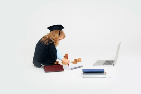 copy book: Little boy child in graduation squared cap and black mantle sitting and drawing by pencil in copy book near box with colored pencils wooden blocks diaries and open notebook isolated