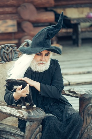 sits: Old man in wizard costume hat for Halloween strokes black cat and sits in wooden chair on log house background
