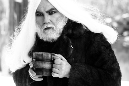 silver hair: Druid old man with long silver hair and beard in fur coat with wooden mug in hands black and white on grey background