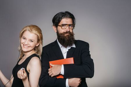 keeps: Elegant couple of smiling young woman in black dress listens to music in smartphone with earphones and handsome bearded hipster man in glasses suit keeps folder on grey wall Stock Photo