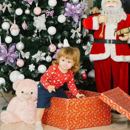 miracle tree: Cute child with gift box in front of the Christmas tree. New year miracle for cute little boy Stock Photo