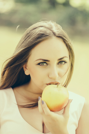 eats: Young beautiful woman eats ripe tasty yellow apple outdoors on sunny summer day