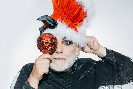 eye ball: New year man with beard on serious face in santa claus hat and black sparkling cloth holding shiny christmas ball opposite his eye posing on white background studio Stock Photo