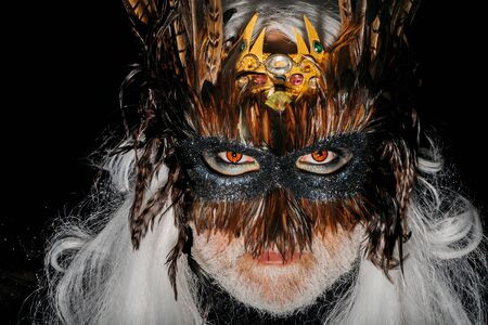 hair feathers: Male face with red eyes white beard and long hair in mysterious decorative vintage carnival mask with brown feathers on black background studio