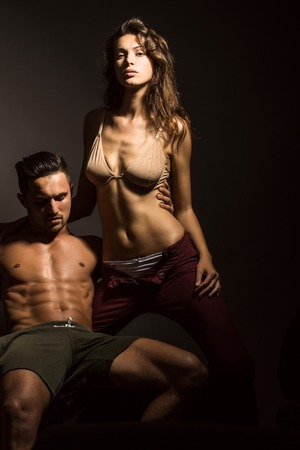desire: young sexy couple of pretty woman in beige bra with wet hair and handsome macho man with muscular torso and athletic body in studio on grey background Stock Photo