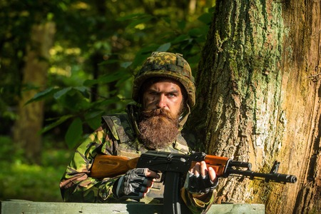 face guard: Young soldier hipster with beard on dirty tired face in military ammunition and helmet standing on guard near tree and wooden board with gun in hands in forest Stock Photo