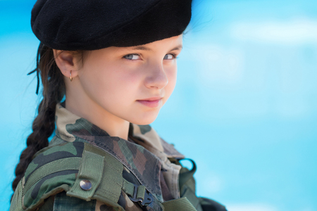 standoff: Young girl child with pretty serious face brunette in army ammunition black beret on blue background outdoor