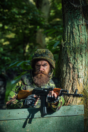 army face: Young soldier hipster with beard on dirty tired face in military ammunition and helmet standing on guard near tree and wooden board with gun in hands in forest Stock Photo