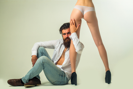 man ass: handsome bearded man with long beard on serious face sitting near sexy female legs and buttocks in lingerie and shoes of young pretty girl in studio isolated on white background, copy space