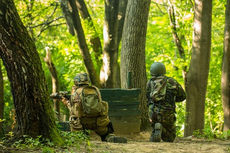 standoff: Two soldiers in military uniform ammunition with armed rifle sitting back and shooting near wooden block post and trees in forest Stock Photo