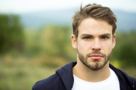 brown hair blue eyes: Young guy with bearded handsome serious face blue eyes brown hair in dark hoody posing outdoor on natural background