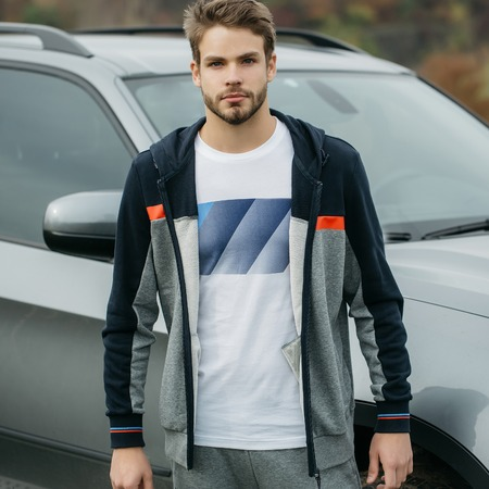 hoody: Young man with handsome serious bearded face wearing dark blue and gray sports hoody and white t shirt posing on background of car outdoor