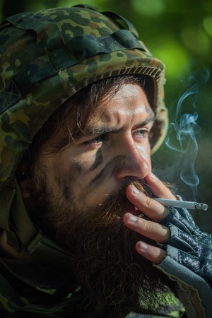 standoff: Soldier man with beard on dirty tired face in military camouflage and helmet holding cigarette by hand and smoking outdoor closeup