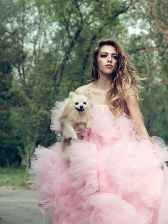 outdoor glamour: Young woman with beautiful face and long curly hair in glamour pink dress holding cute small dog outdoor with green trees