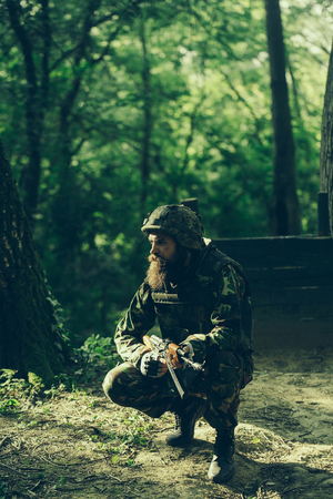 standoff: Young soldier man with beard on thoughtful face in army ammunition and helmet with rifle sitting on hos haunches in forest on green trees background Stock Photo