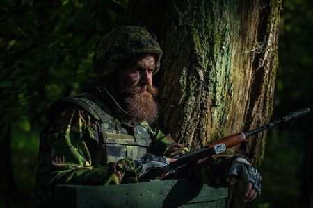 standoff: Young soldier with beard on dirty tired face in military uniform and helmet with rifle on tree and green forest background outdoor Stock Photo