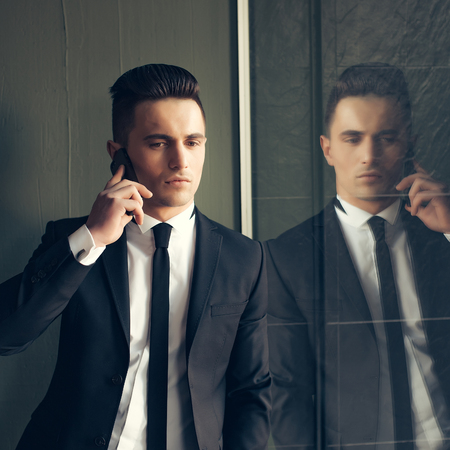 conversa: Man young handsome sensual elegant model in suit with skinny necktie open coat talks on mobile phone looks down hand in pocket reflects in mirror on grey background