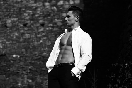 trouser: Man half face bare-chested young handsome sensual model in shirt gaped open poses with hands in trouser pockets outside black and white on masonry background