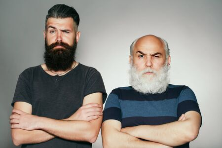 eyebrow raised: Old and young bearded men with long beard white and brown and raised eyebrow in studio on grey background