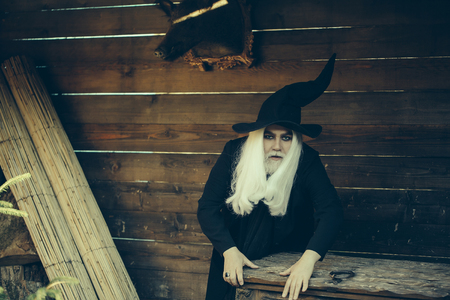 chest hair: Old man wizard with long grey hair beard in black costume and hat for Halloween standing near wooden chest or trunk box on log house background Stock Photo