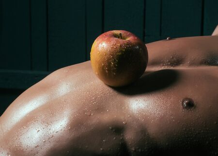 sexy pose: Muscular young man with apple fruit on athletic bare torso closeup, healthy food and diet
