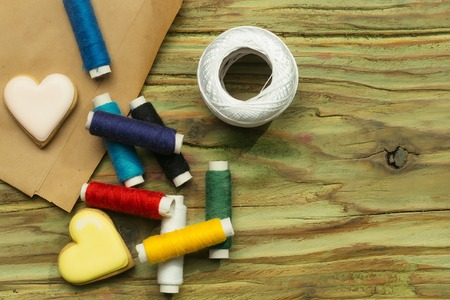 pack string: Group of bobbins of cotton colorful thread two homemade cookies in shape of heart and hank of yarn laying on pack paper and wooden background