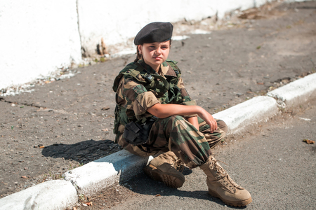 aggressiveness: Young girl child with pretty sad thoughtful face in army camouflage ammunition and black beret sitting on stone ground outdoor Stock Photo