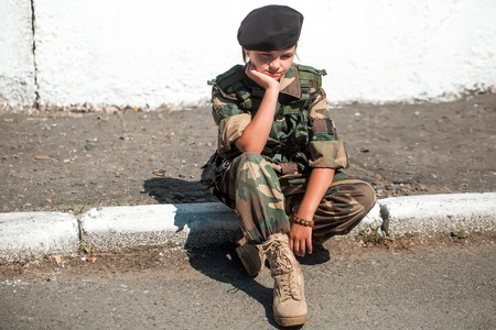 standoff: Young girl child with pretty sad thoughtful face in army camouflage ammunition and black beret sitting on stone ground outdoor Stock Photo