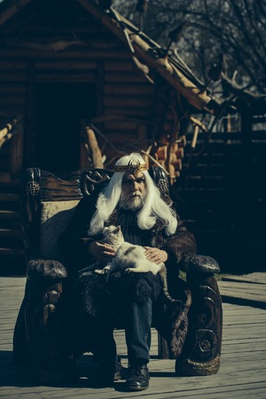 druid: Druid old man with long grey hair beard with crown in fur coat holds cat and sits in wooden chair on log house background