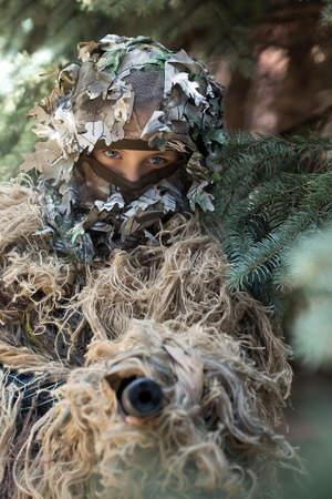 defender: Young girl soldier defender with blue eyes face closed by mask in ghillie camouflage military ammunition with gun standing on background of spruce tree