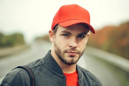 Hombre joven con barba en su cara seria seria en chaqueta casual oscura y gorra de béisbol roja en la cabeza en el fondo de la manera de camino al aire libre Foto de archivo