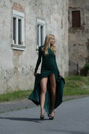 young pretty woman with long lush curly blonde hair and bodies in green dresses walking near stony building with windows outdoor