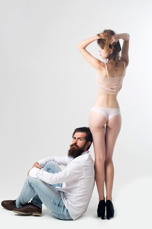 man ass: handsome bearded man with long beard and moustache on serious face sitting near young pretty girl with sexy legs and buttocks in lingerie in studio isolated on white background, copy space
