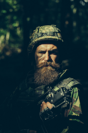 standoff: Young soldier with sad bearded face in military helmet and camouflage with gun on forest background