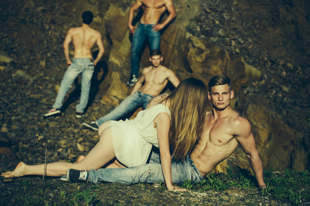 macho: four handsome young macho men with muscular body and six packs on torso in jeans and pretty woman in white dress sunny day outdoor on stony natural background
