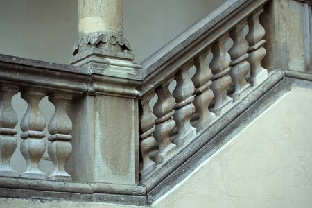 parapet: Stone balustrade of old baroque parapet as handrail of staircase and column on grey background