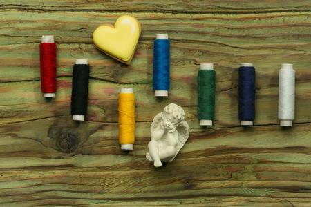trabajo manual: Conjunto de bobinas de coser de puntada de colores para galletas trabajo hecho a mano en forma de coraz�n y la figura de �ngel en el fondo de madera