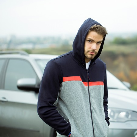 hoody: Young man with handsome bearded serious face in casual dark blue and gray hoody with hood on his head posing with hands in pockets on car background outdoor Stock Photo