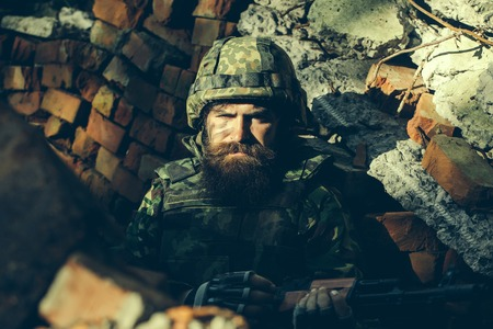 standoff: Soldier man with tired dirty bearded face in army ammunition and helmet holding gun in hands sitting in stone brick ruins Stock Photo