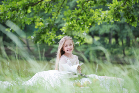 prom queen: small girl kid with long blonde hair and pretty smiling happy face in prom princess white dress standing sunny day outdoor on natural background with fruit basket of red apples peach and cherry and book