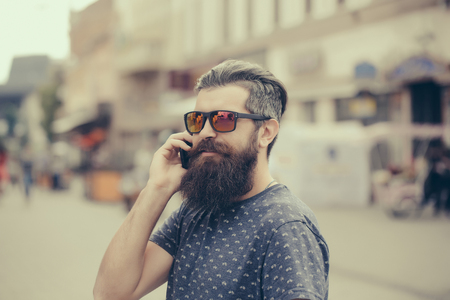 hairy closeup: handsome bearded young man hipster with long beard and mustache has stylish hair on smiling hairy face in sun glasses speaking on mobile phone outdoor, closeup
