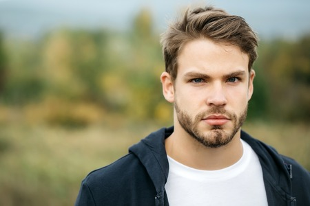 Young guy with bearded handsome serious face blue eyes brown hair in dark hoody posing outdoor on natural background Stok Fotoğraf - 62479712