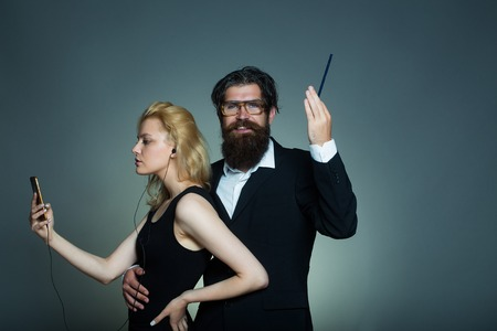 splendid: Attractive couple of young woman with mobile and handsome smiling man with splendid beard holding pen posing on gray background indoor Stock Photo