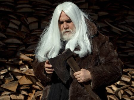 woodpile: Old man druid with long silver hair and beard in fur coat stands with axe on woodpile background