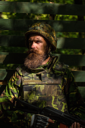 standoff: Young soldier with sad bearded face in military helmet and camouflage with gun on wooden background Stock Photo