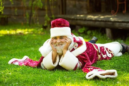 lies: Smiling man santa claus in Christmas new year red suit and hat lies on green grass on natural background